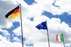 Σημαίες της Ευρώπης, της Γερμανίας και της Ιταλίας Ουρανός και σύννεφα όπως ένα υπόβαθρο Κυματίζοντας σημαίες σύνορα Στοκ φωτογραφία με δικαίωμα ελεύθερης χρήσης