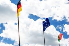 Σημαίες της Ευρώπης, της Γερμανίας και της Ιταλίας Ουρανός και σύννεφα όπως ένα υπόβαθρο Κυματίζοντας σημαίες σύνορα Στοκ Φωτογραφία