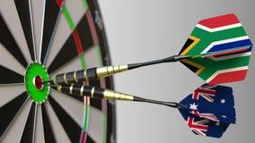 Σημαίες της Νότιας Αφρικής και της Αυστραλίας στα βέλη που χτυπούν bullseye του στόχου Διεθνής συνεργασία ή ανταγωνισμός Στοκ Εικόνες