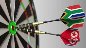Σημαίες της Νότιας Αφρικής και της Βόρεια Κορέας στα βέλη που χτυπούν bullseye του στόχου Διεθνής συνεργασία ή ανταγωνισμός Στοκ Εικόνες