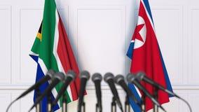 Σημαίες της Νότιας Αφρικής και της Βόρεια Κορέας στη διεθνή συνεδρίαση ή τη διάσκεψη τρισδιάστατη απόδοση Στοκ Φωτογραφίες