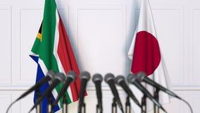 Σημαίες της Νότιας Αφρικής και της Ιαπωνίας στη διεθνή συνεδρίαση ή τη διάσκεψη τρισδιάστατη απόδοση Στοκ Εικόνες