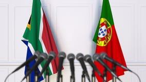 Σημαίες της Νότιας Αφρικής και της Πορτογαλίας στη διεθνή συνεδρίαση ή τη διάσκεψη τρισδιάστατη απόδοση Στοκ Φωτογραφίες