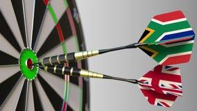 Σημαίες της Νότιας Αφρικής και του Ηνωμένου Βασιλείου στα βέλη χτυπώ bullseye του στόχου Διεθνής συνεργασία ή Στοκ Εικόνες