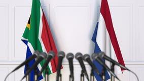 Σημαίες της Νότιας Αφρικής και των Κάτω Χωρών στη διεθνή συνεδρίαση ή τη διάσκεψη τρισδιάστατη απόδοση Στοκ Εικόνες