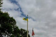 σημαίες των ΗΠΑ και της Ουκρανίας ενάντια στο φωτεινό μπλε ουρανό Στοκ εικόνες με δικαίωμα ελεύθερης χρήσης