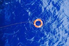 Σημαντήρας ζωής που δεσμεύεται με τη διάσωση σχοινιών που επιπλέει στη θάλασσα Στοκ Εικόνες