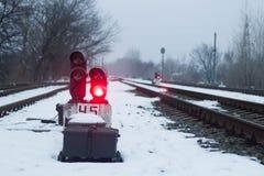 Σηματοφόρος στο σιδηρόδρομο το χειμώνα, κόκκινο πυράκτωσης Θλιβερή σκηνή στοκ εικόνες