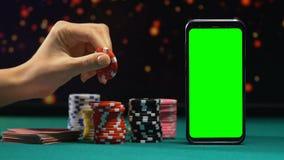 Σημεία και κάρτες χαρτοπαικτικών λεσχών που βρίσκονται κοντά στο πράσινο smartphone οθόνης, on-line που παίζει φιλμ μικρού μήκους