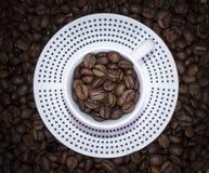 Σημεία Πόλκα φλυτζανιών που στέκονται στα φασόλια καφέ Θαμπάδα, τοπ άποψη Στοκ Φωτογραφίες