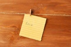 Σημείωση αγάπης για την καρφίτσα στο ξύλινο υπόβαθρο Στοκ Φωτογραφία