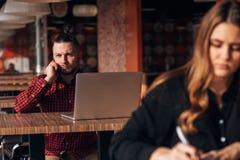 Σημείωση γραψίματος επιχειρησιακών νέων κοριτσιών στο σημειωματάριο στον καφέ, άτομο με το lap-top στο υπόβαθρο στοκ εικόνα