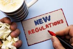 Σημείωση γραψίματος που παρουσιάζει νέους κανονισμούς Την αλλαγή επίδειξης επιχειρησιακών φωτογραφιών των εταιρικών προδιαγραφών  Στοκ Εικόνες