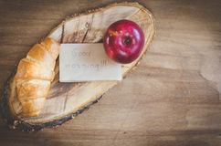 Σημείωση της Apple, Croissant και καλημέρας για το αγροτικό ξύλινο υπόβαθρο Στοκ Εικόνα