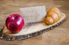 Σημείωση της Apple, Croissant και καλημέρας για το αγροτικό ξύλινο υπόβαθρο Στοκ φωτογραφίες με δικαίωμα ελεύθερης χρήσης