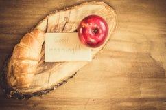 Σημείωση της Apple, Croissant και καλημέρας για το αγροτικό ξύλινο υπόβαθρο Στοκ Εικόνες