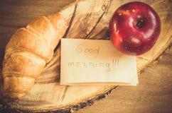 Σημείωση της Apple, Croissant και καλημέρας για το αγροτικό ξύλινο υπόβαθρο Στοκ φωτογραφία με δικαίωμα ελεύθερης χρήσης