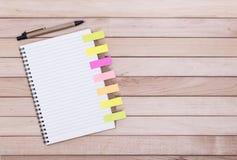 Σημειωματάρια με τις αυτοκόλλητες ετικέττες στο υπόβαθρο των ξύλινων πινάκων Στοκ φωτογραφία με δικαίωμα ελεύθερης χρήσης