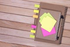 Σημειωματάρια με τις αυτοκόλλητες ετικέττες στο υπόβαθρο των ξύλινων πινάκων Στοκ Εικόνα