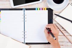 Σημειωματάριο γραψίματος χεριών ατόμων στον ξύλινους πίνακα και το φλυτζάνι του καυτού καφέ Στοκ εικόνα με δικαίωμα ελεύθερης χρήσης