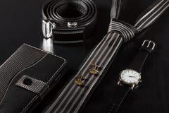 Σημειωματάριο, δεσμός, μανικετόκουμπα, ζώνη δέρματος, ρολόι σε ένα μαύρο backgro Στοκ Φωτογραφία