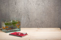 Σημειωματάριο και γυαλιά δεξαμενών ψαριών στον πίνακα ξύλινο Στοκ Εικόνες