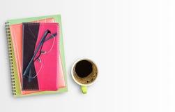 Σημειωματάριο και γυαλιά με το φλιτζάνι του καφέ στο γραφείο γραφείων Στοκ Φωτογραφία