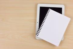 Σημειωματάριο και ηλεκτρονική συσκευή εγγράφου στον ξύλινο πίνακα Στοκ Εικόνα