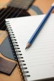 Σημειωματάριο και μολύβι κινηματογραφήσεων σε πρώτο πλάνο στην κιθάρα Στοκ Φωτογραφίες