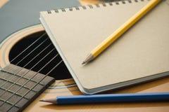 Σημειωματάριο και μολύβι κινηματογραφήσεων σε πρώτο πλάνο στην κιθάρα Στοκ εικόνα με δικαίωμα ελεύθερης χρήσης