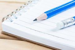 Σημειωματάριο και μολύβι κινηματογραφήσεων σε πρώτο πλάνο στον ξύλινο πίνακα Στοκ Εικόνα
