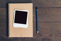 Σημειωματάριο και μολύβι με τη φωτογραφία πλαισίων στο ξύλινο επιτραπέζιο υπόβαθρο Στοκ Εικόνες