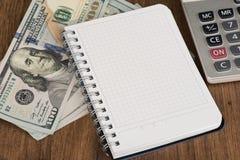 Σημειωματάριο και δολάρια με το διάστημα αντιγράφων Στοκ Φωτογραφία