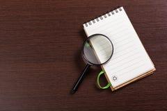 Σημειωματάριο και πιό magnifier Στοκ φωτογραφίες με δικαίωμα ελεύθερης χρήσης