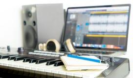 Σημειωματάριο και πληκτρολόγιο μουσικής στον υπολογιστή γραφείου στούντιο μουσικής για το συγγραφέα τραγουδιού Στοκ Εικόνα