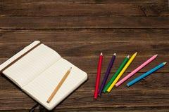Σημειωματάριο και χρωματισμένα μολύβια σε έναν ξύλινο πίνακα Στοκ φωτογραφία με δικαίωμα ελεύθερης χρήσης