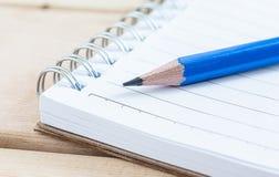 Σημειωματάριο κινηματογραφήσεων σε πρώτο πλάνο και μπλε μολύβι στον ξύλινο πίνακα Στοκ Φωτογραφία