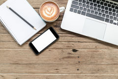 Σημειωματάριο, κινητά τηλέφωνο και lap-top στον ξύλινο πίνακα Στοκ φωτογραφία με δικαίωμα ελεύθερης χρήσης