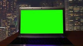 Σημειωματάριο με μια πράσινη οθόνη σε ένα σκοτεινό δωμάτιο απόθεμα βίντεο