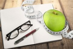 Σημειωματάριο με να μετρήσει την ταινία και ένα μήλο επάνω Στοκ εικόνες με δικαίωμα ελεύθερης χρήσης