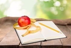 Σημειωματάριο με να μετρήσει την ταινία και ένα μήλο επάνω Στοκ Εικόνες