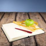 Σημειωματάριο με να μετρήσει την ταινία και ένα μήλο επάνω Στοκ Εικόνα
