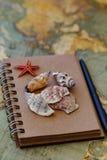 Σημειωματάριο με τα θαλασσινά κοχύλια και τη μαύρη μάνδρα Στοκ Εικόνες