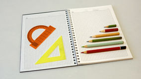 Σημειωματάριο με τα μολύβια και τους κυβερνήτες σε ένα ελαφρύ υπόβαθρο Στοκ εικόνα με δικαίωμα ελεύθερης χρήσης