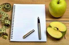 Σημειωματάριο με τα πράσινα φρούτα και το εκατοστόμετρο μήλων Στοκ φωτογραφία με δικαίωμα ελεύθερης χρήσης