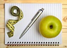 Σημειωματάριο με τα φρούτα εκατοστόμετρων και μήλων Στοκ φωτογραφία με δικαίωμα ελεύθερης χρήσης