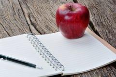 Σημειωματάριο με τα φρούτα μανδρών και μήλων στον πίνακα Στοκ φωτογραφία με δικαίωμα ελεύθερης χρήσης