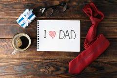 Σημειωματάριο με την επιγραφή Ι DAD αγάπης, φλιτζάνι του καφέ, γυαλιά, κιβώτιο δώρων και δεσμός στο ξύλινο υπόβαθρο, διάστημα για στοκ φωτογραφίες