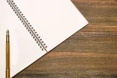 Σημειωματάριο με την κενή σελίδα και χρυσή μάνδρα στον ξύλινο πίνακα Στοκ Φωτογραφία