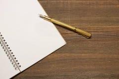 Σημειωματάριο με την κενή σελίδα και χρυσή μάνδρα στον ξύλινο πίνακα Στοκ φωτογραφία με δικαίωμα ελεύθερης χρήσης